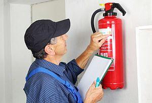 Fachmann bei der Prfung eines Feuerlschers